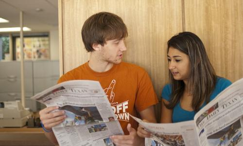 Students reading The Daily Texan.