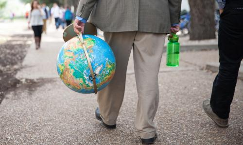 Person walking on sidewalk carrying a globe.
