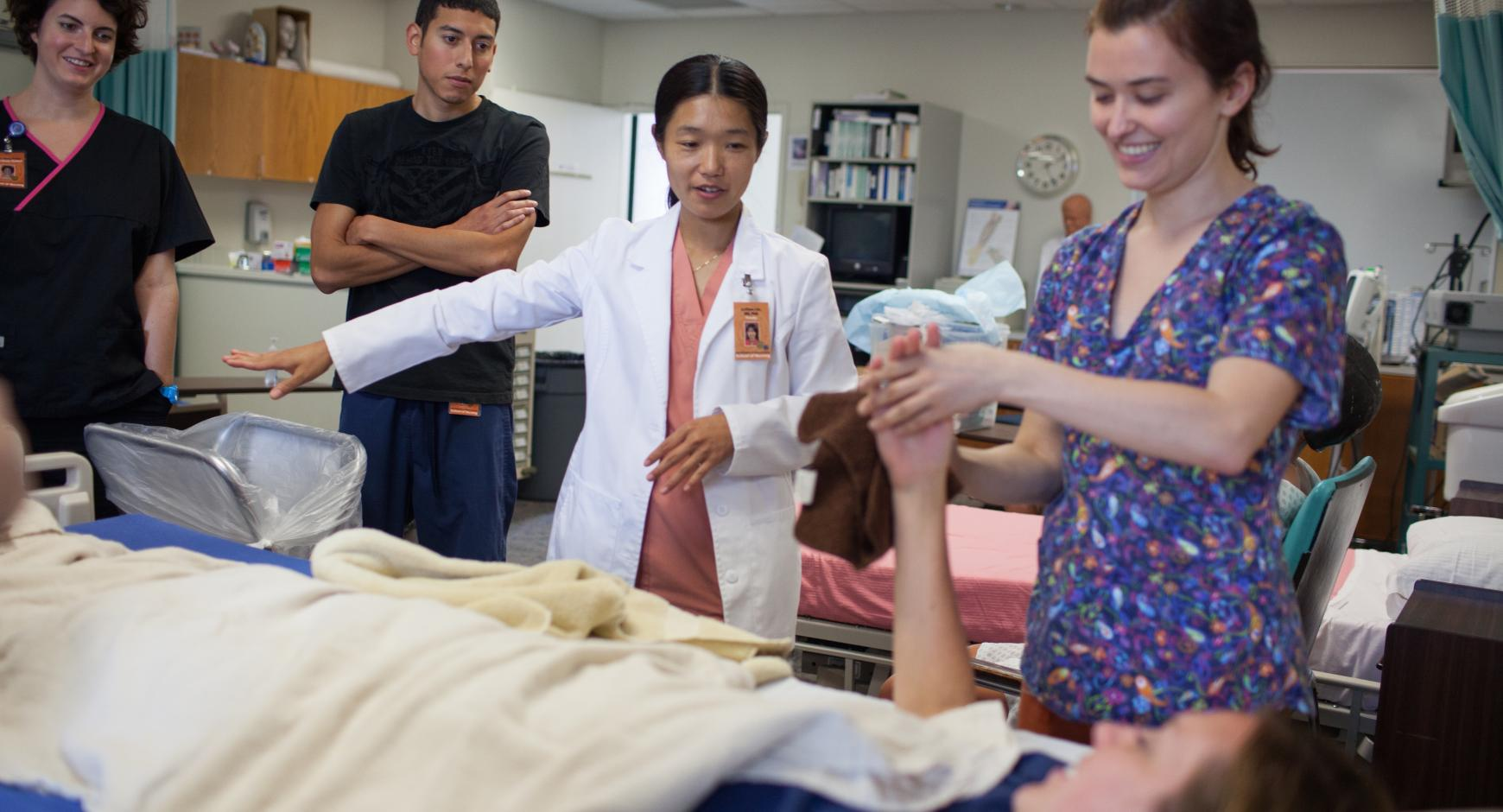 Nursing students receive instruction while helping a patient.