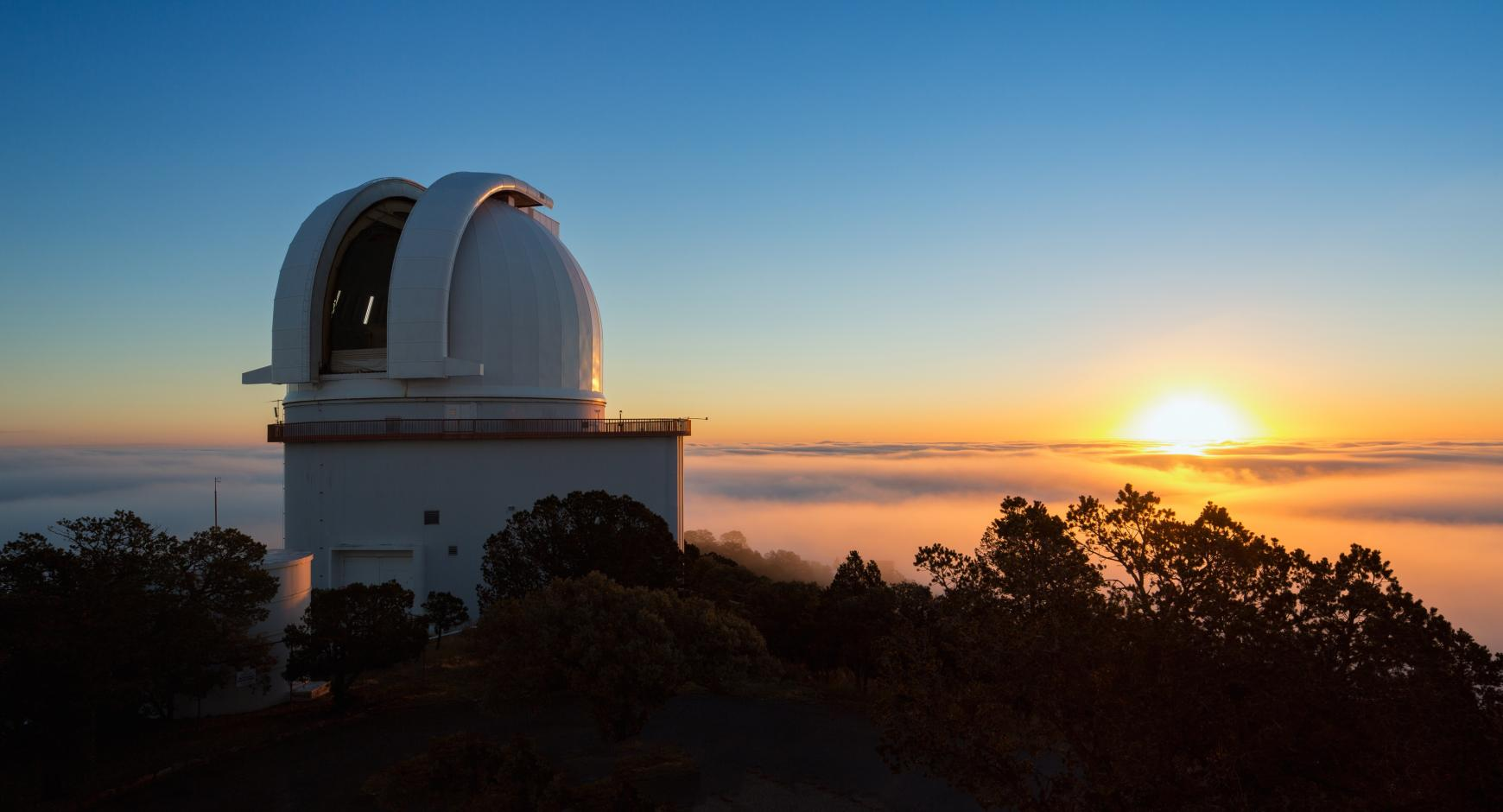 The Sun rises behind the open dome of the Harlan J. Smith Telescope