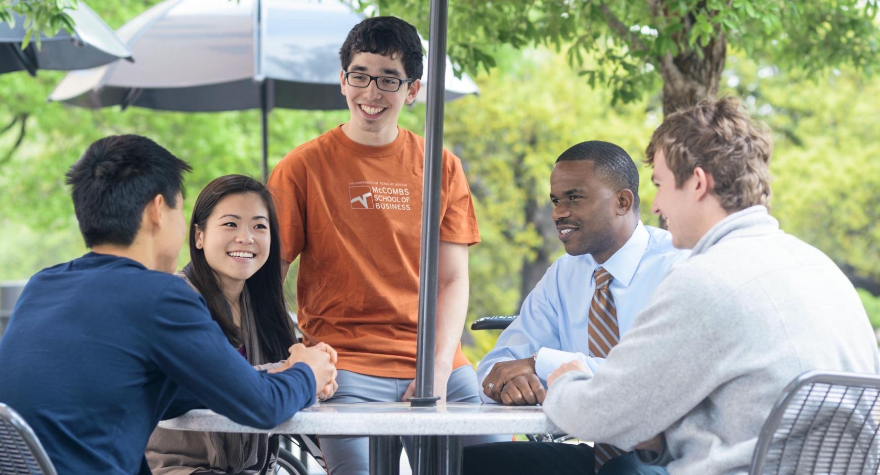 A group of McCombs students chat with each other outside of the school.