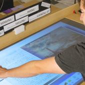Student examines archived work on large touch screen display.