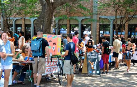 Students browsing student organization tables at Party on the Plaza