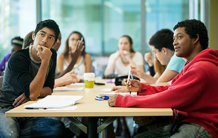 Undergraduate students sitting at table and listening to speaker.