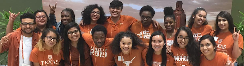 Smiling group of UT students wearing burnt orange shirts